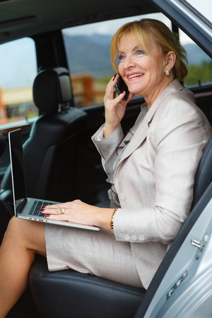 60 65 years: Happy and smile old senior business woman 60-65 years with white teeth, talking by mobile cell phone in the back of a car and holding her Laptop Computer pc in lap