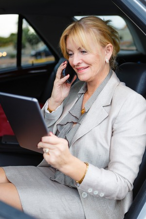 ibook: Closeup portrait of smiling happy old senior business woman 6065 years sitting in car holding her Tablet PC computer and talking by mobile phone looking to screen Stock Photo
