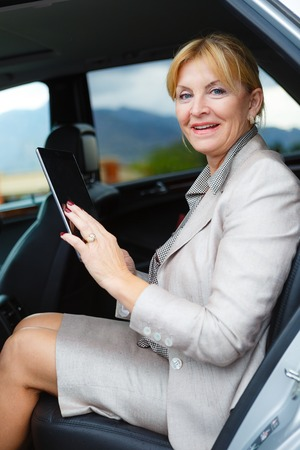 ibook: Old senior business woman 6065 years sitting in car holding her Tablet PC computer and looking to camera Stock Photo