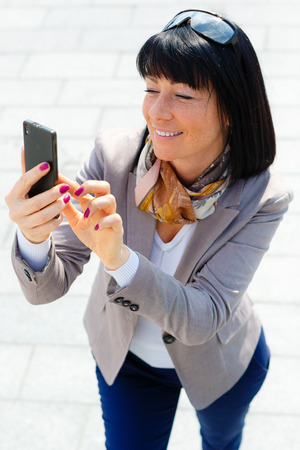 lose up: –°lose up portrait Happy, cheerful and smile, brunette woman, excited by what she sees on cell phone, Facial expression, reaction. Business woman sending text message from her mobile Stock Photo