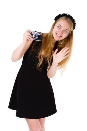 Smile and happy young blonde woman taking a picture with an old camera and waves a hand isolated on white Positive human emotion facial expression photo