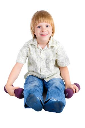 blonde yeux bleus: Sourire mignon jeune petit garçon est assis sur le sol et joue avec des haltères, isolé sur fond blanc, l'émotion humaine positive, l'expression du visage