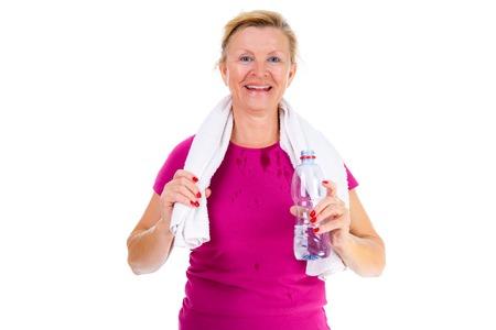 mujeres maduras: Sonrisa mayor de la mujer de edad de edad avanzada en equipo del deporte después del ejercicio físico en el gimnasio con una botella de agua en la mano y una toalla alrededor del cuello, aislados en fondo blanco, las emociones humanas positivas