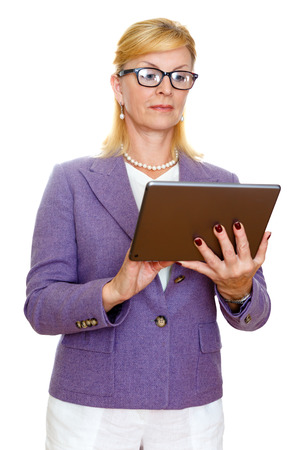 ibook: Old senior business woman 60-65 years in glasses and suit, using digital tablet pc computer reading ebook. Isolated on white background
