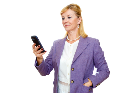 65 years old: Happy 65 years old senior business woman in suit. Holding cell phone, smartphone in hand read and write sms. Isolated, plain white background