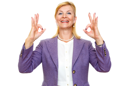 60 65 years: Happy smiling old senior woman 60-65 years with white teeth, shows gesture ok on two hands. In suit with big blue eyes, isolated on white background, Positive human emotion, facial expression Stock Photo