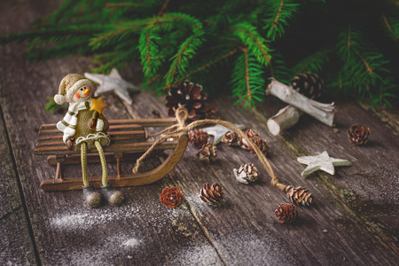 Xmas or new year composition with holiday decoration - sledge, little man figures and fir branches, pinecones on wooden background.