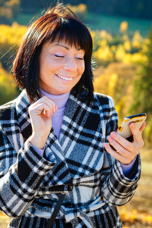 woman 40 years: Cheerful fashion woman 40 years old wearing warm clothes in autumn. Beautiful brunette with autumn coat. Smiled and reading sms on her smartphone, Gold autumn background