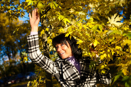 40 years old: Elegant and smiled brunette fashion woman 40 years old wearing warm clothes in the autumn forest, Gold autumn background