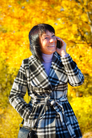 woman 40 years: Cheerful fashion woman 40 years old wearing warm clothes in autumn. Beautiful brunette with autumn coat. Smiled and talking by cell phone, Gold autumn background Stock Photo