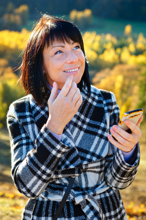 woman 40 years: Cheerful fashion woman 40 years old wearing warm clothes in autumn. Beautiful brunette with autumn coat. Smiled and writing sms on her smartphone, Gold autumn background