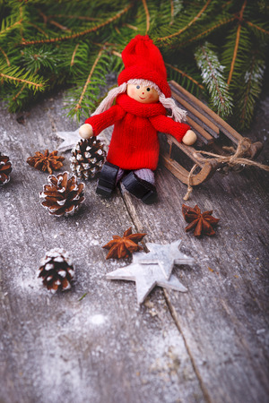 Xmas or new year composition with holiday decoration - sledge, little man figures, fir branches and pinecones on wooden background.