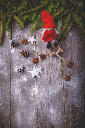 tinting: Xmas or new year composition with holiday decoration - sledge, little man figures, fir branches and pinecones on wooden background.