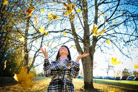 gente feliz: Mujer morena de manera feliz y sonrió llevaba ropa de abrigo en el bosque de otoño, fondo de otoño del oro