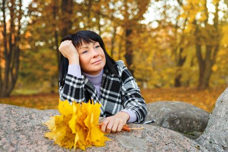 woman 40 years: Elegant brunette woman 40 years old with bouquet of maple leaves in hand, wearing warm clothes in the autumn forest, Gold autumn background Stock Photo