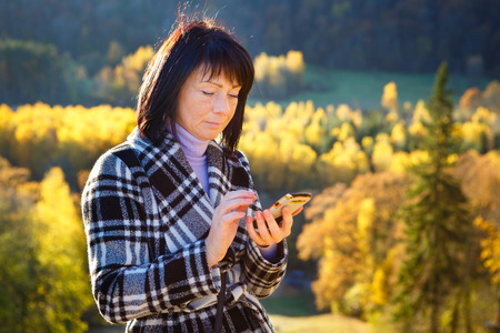 woman 40 years: Cheerful fashion woman 40 years old wearing warm clothes in autumn. Beautiful brunette with autumn coat. Focus on her smartphone, write sms. Gold autumn background
