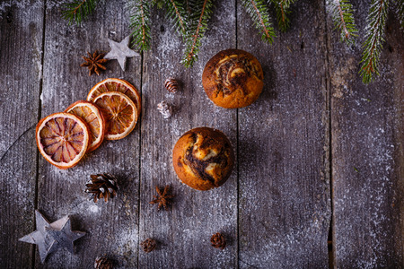 pinecones: Xmas or new year composition with holiday decoration - Homemade christmas cupcakes, sliced dried oranges on wooden background with spruce twigs and pinecones. Christmas card. Space for text