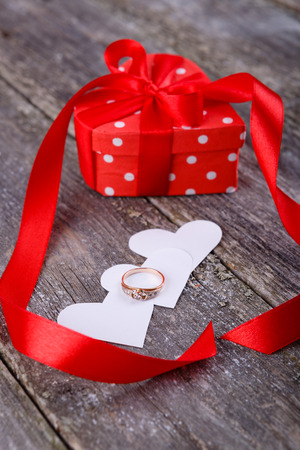 dimond: Valentines Day background - gold dimond ring on white hearts and little box with red bow on old wooden background Stock Photo