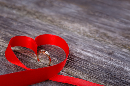 dimond: Valentines Day background - red ribbon of heart with gold dimond ring on old wooden background