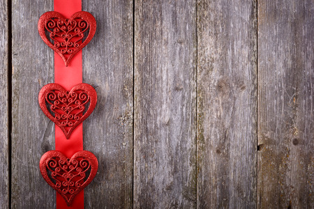 text space: Valentines Day background - big hearts on red ribbon on wooden background. Text space