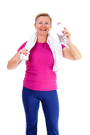 55 years old: Image of old senior woman in sport outfit with white towel on her neck drinking water, isolated on white background, Positive human emotions