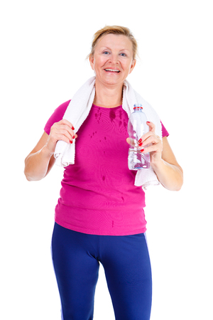 65 years old: Image of old senior woman in sport outfit with white towel on her neck drinking water after fitness exercises, isolated on white background, Positive human emotions