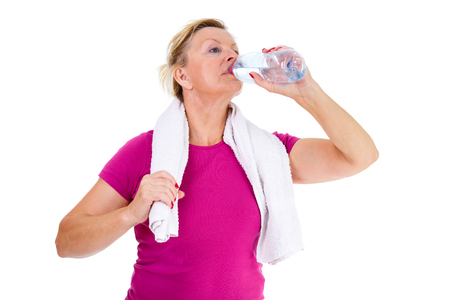 65 years old: Image of old senior woman in sport outfit with white towel on her neck drinking water, isolated on white background, Positive human emotions