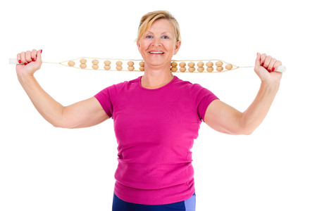 stretchy: Happy and smile old senior woman dressed in t-shirt color Marsala doing sport fitness exercises with manual wooden masseur for massage of a neck, isolated on white background, Positive emotions