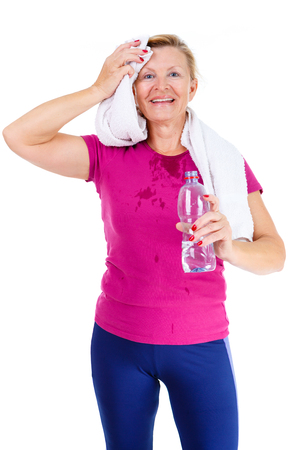 55 years old: Happy and smile old senior woman in sport outfit marsala color with white towel on her neck, hold water bottle in hand and mop ones brow after fitness exercises, isolated on white background