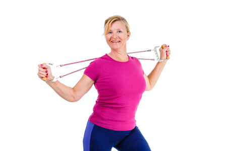 stretchy: Happy and smile old senior blond woman dressed in shirt color Marsala doing fitness exercises with expander a resistance band, isolated on white background, Positive human emotions