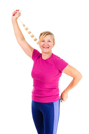 stretchy: Happy and smile old senior woman dressed in t-shirt color Marsala doing sport fitness exercises with manual wooden masseur for massage of a back, isolated on white background, Positive emotions