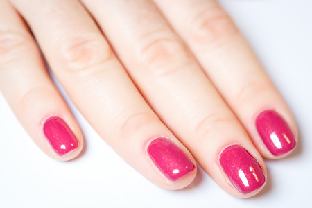manicured hands: Manicure - Beautiful manicured womans hands with red nail polish on soft white towel.