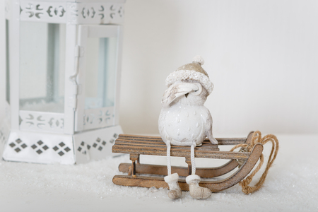 Xmas or new year composition with holiday decoration - lamp and little owl figure sitting on sledge on white background. Xmas card