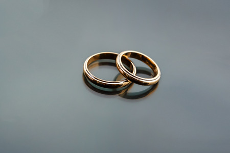 jewelle: Celebratory accessories - two gold wedding rings for special day on glass grey background Stock Photo
