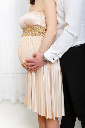 Holiday composition. Married pregnant woman and man or couple holding hands. Big belly, 6, 7, 8, 9 months pregnant. In yellow, baige, gold dress. Man in white shirt and black pants.  Stock Photo
