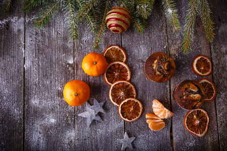 Xmas composition with holiday decoration - Homemade christmas cupcakes, sliced dried oranges on wooden background with spruce twigs and christmas toy. Christmas card. Space for text Stock Photo