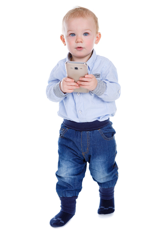 Happy and smiling excited baby boy goes and holding smartphone. Child wants to play. Isolated on white background Stock Photo
