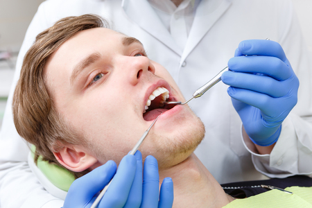 Closeup portrait of Young Man in dentist chair having teeth examined at dentists in dental office