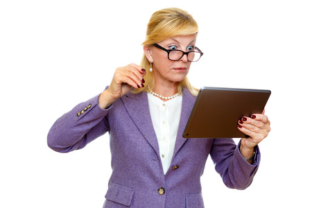 Surprised old senior business woman 60-65 years in glasses and suit, using digital tablet pc computer reading ebook. Isolated on white background