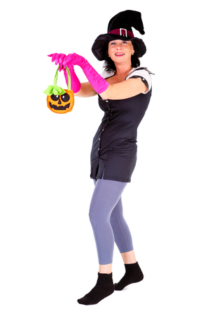 Woman dressed in Halloween witch costum carnaval, show emotions of witch on white isolated background Stock Photo
