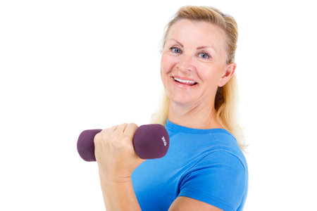 Pensioner woman sport. Old senior woman dressed in blue t-shirt. Woman looking at camera, holding dumbbells and cheerfully smiling while doing sport exercises. isolated on white background