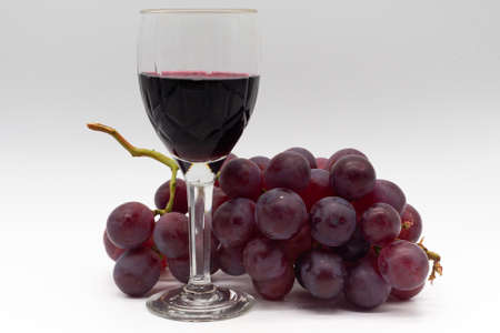 Glass of red wine with bunch of red grapes on white background