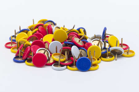 Colored thumbtacks on white background. Product photo. Office supplies.