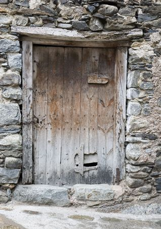An ancient door in a rustic stone wall photo