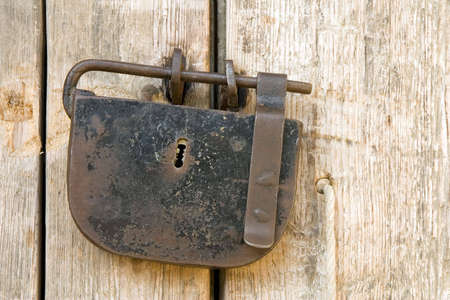 A rusty ancient padlock on a wooden door photo