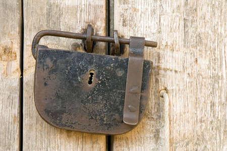 padlocked: A rusty ancient padlock on a wooden door