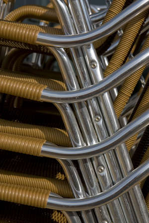 stackable: Close-up of stacked metal chairs outside a bar