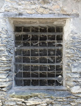 weatherworn: An ancient window with a rusty grid