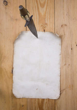 Old paper pinned to a wooden wall  with a dagger