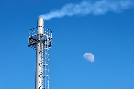 High chimney made of stainless steel of an industrial gas boiler with smoke coming out of it (steam). Steel platform and vertical ladder for maintenance. Clear evening sky with the rising moon.